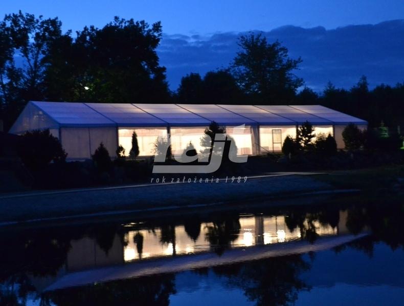 Hala namiotowa przy jeziorze nocą.
